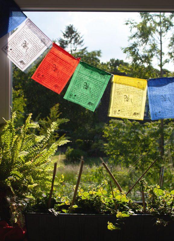 Tibetische Gebetsahnen vor dem Fenster aufhängen
